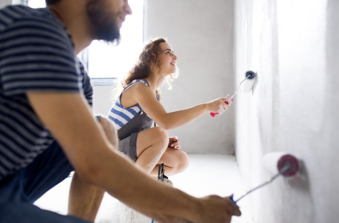 young couple painting walls in their house during a home makeover